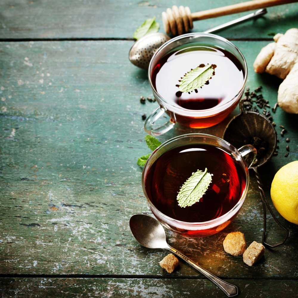 Tea with mint, ginger and lemon on old wooden table